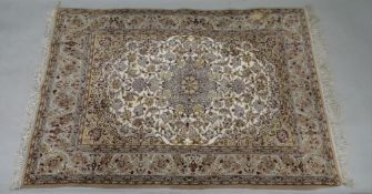A modern Kashan rug, with a central medallion surrounded by flowering branches, on an ivory ground,