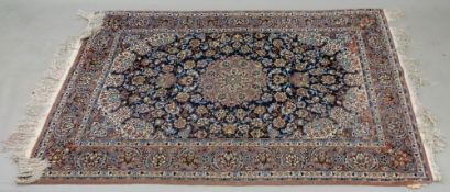 A modern Kashan rug, with a central medallion surrounded by flowering branches, on a blue ground,