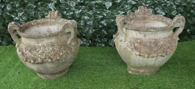 A pair of reconstituted stone tyg style jardinieres with three loop handles and floral moulded body,