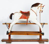 A wooden grey painted rocking horse, early 20th century, on a stained pine base,