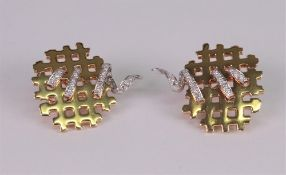 A pair of 18ct white and yellow gold and diamond set earclips of abstract lattice design,