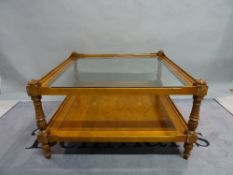 A modern stained beech and walnut two tier square coffee table with glass top,