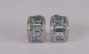 A pair of precious white metal, aquamarine and diamond set earclips of half hoop design,
