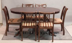 A modern Regency style mahogany twin pillar dining table together with six matching chairs,