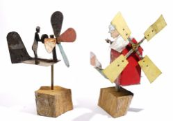 Two primitive/folk art whirlygigs both modelled as a person cranking a windmill, approx 35cm high.