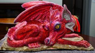 A fairground model of a dragon decorated in red and pink glitter, the head articulating,