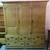 A late George III pine triple wardrobe with three paneled doors over an arrangement of five drawers,