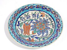 An Iznik style earthenware dish, probably late 19th century, painted with a tulip,