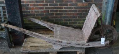 A 19th century hardwood barrel wheelbarrow, 210cm wide x 87cm high.