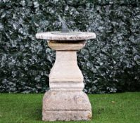 A cast bronzed sundial on a stone square baluster column,