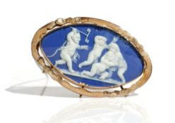 A gold mounted oval blue and white jasperware cameo brooch, designed as a group of three putto,