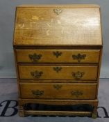 An early 20th century bureau with three long drawers on block supports, 74cm wide x 104cm high.