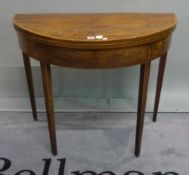 A George III mahogany demi-lune foldover card table on tapering square supports,