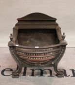 A cast iron bowfront fire basket with tapered finials, 57cm wide.