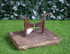 A wrought iron boot scraper on stone mount, 39cm wide x 25cm high.