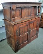 A 17th century oak court cupboard with two pairs of panelled cupboards flanked by turned cloumns,