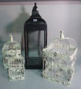 A group of three modern hanging bird cages, the largest 70cm x 21cm and a candle lantern, (4).
