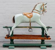 An early 20th century green painted wooden rocking horse with a tan saddle and glass eyes,