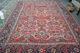 A Mahal carpet, Persian, the madder field with an allover palmette and floral vine design,