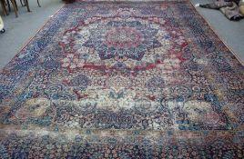 A Kerman carpet, Persian, the madder field with a bold rosette medallion, indigo spandrels,