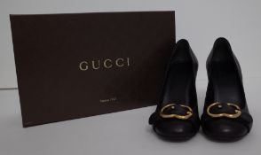A pair of lady's Gucci black leather high heeled court shoes with gold-tone hardware G buckles,