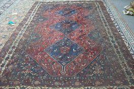 A Shiraz carpet, Persian the madder field with three indigo diamonds,