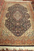 An Indian rug of Persian design, the dark indigo field with a pale medallion, ivory spandrels,