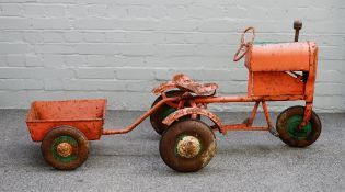 A mid-20th century Triang tin plate pedal tractor and cart,