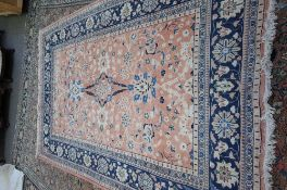 A Persian rug, the pale madder field with two bold palmettes and floral sprays,