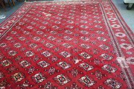 A Bokhara carpet with all over design and sunburst border, 395cm x 300cm.