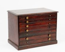 A 19th century mahogany table top collector's chest of seven long graduated drawers on a plinth