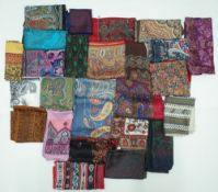 A large collection of twenty-five silk and wool scarves each printed with a paisley design,