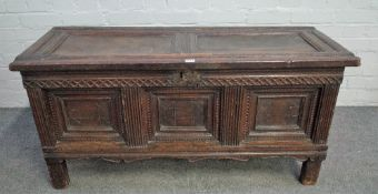 A 17th century oak coffer with twin panel lid over triple moulded panel front on stile feet,