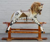 A wooden dapple grey painted rocking horse, early 20th century, on a stained pine base,