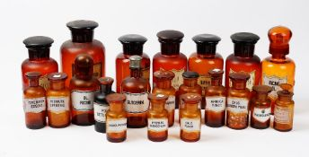 A collection of twenty one 20th century brown and amber glass apothecary jars,