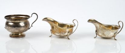 A pair of silver sauce boats each raised on three feet Birmingham 1964 and a sliver sugar bowl