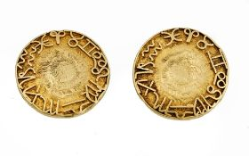 A pair of yellow precious metal dress studs, applied with zodiac symbols, to a textured ground,