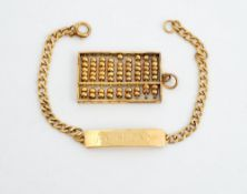 A gold pendant, designed as an abacus, detailed 14 K and a gold faceted curb link identity bracelet,