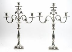 A pair of French three light table candelabra, each light with an octagonal drip pan,