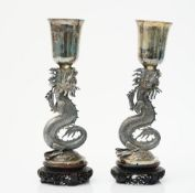 A pair of Chinese vases, each supported by an open mouthed dragon, raised on a circular base,