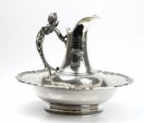 A French silver toilet jug and bowl, the jug decorated to the body with two oval reserves,