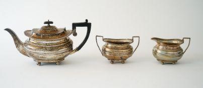 A silver three piece tea set comprising; a teapot, a twin handled sugar bowl and a milk jug,