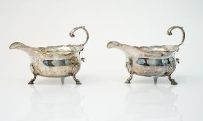 A George III pair of silver sauceboats, each having a shaped rim,
