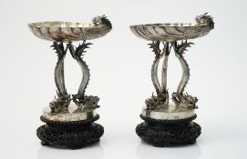 A pair of Chinese sweetmeat stands, each formed as a scallop shell with a dragon's head to the side,