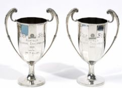 A pair of silver twin handled trophy cups, each of multi-sided form with foliate capped handles,