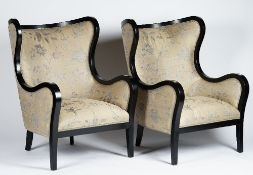 A pair of contemporary wing armchairs with ebonised frames,