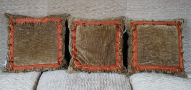 A set of three moss velvet cushions with bobble bands (3).