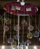 A contemporary light fitting, hung with twelve coloured glass balloons,