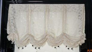 A pair of cream linen Roman blinds hung with black and white bobble tassels.