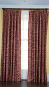 A pair of linen curtains printed with multicoloured designs, with tasseled edging.